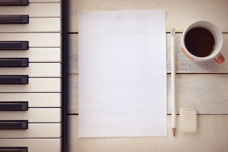Inspirational background with a piano on a wooden table while composing. Score sheet, a pencil and a cup of coffee for the music composer, Top view and a copy space for editor's text. Banque d'images