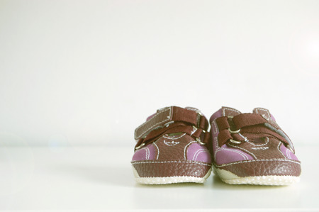 editors: Baby booties on a white wood. White background with a copy space for editors text.