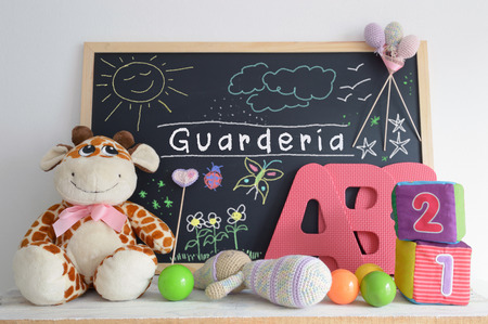 baby stuff: A blackboard in a kindergarten classroom. Some baby stuff . Foam letters , cubes , and hand made drawings.The word GUARDERIA Spanish word that means KINDERGARTEN