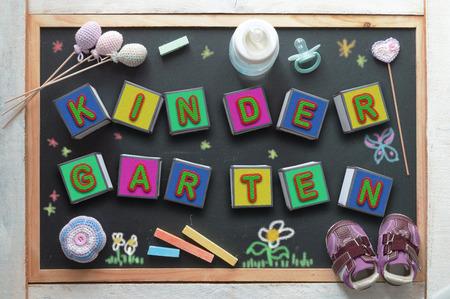kinder: Algunos cubos de letras que forman la palabra jardín de infantes, un biberón, un chupete, algunos juguetes y zapatillas de deporte en un pizarrón negro desde arriba. Objetos relacionados con la educación infantil.
