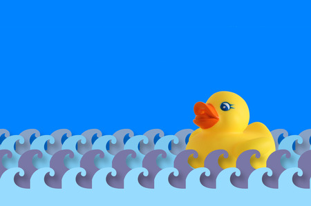 Rubber duck floating on some water waves made of paper. A background representing child care and bathroom time. Empty copy space for editor's text. Banque d'images
