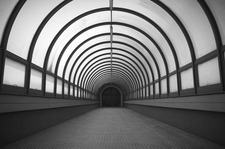 semicircular: Semicircular long corridor. Illuminated way. Black and white.