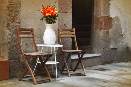 nook: Rustic wooden chairs in the middle of a street in Barcelona, Spain. Peaceful romantic nook.