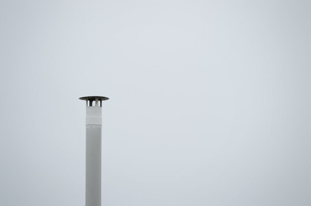 fineart: A smokestack against a grey sky. Empty copy space for editors text.