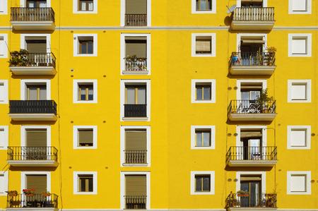 Gelbe Fassade. Einige ausgerichtete Wohnung Fenster machen Reihen. Sonniger Tag. Standard-Bild