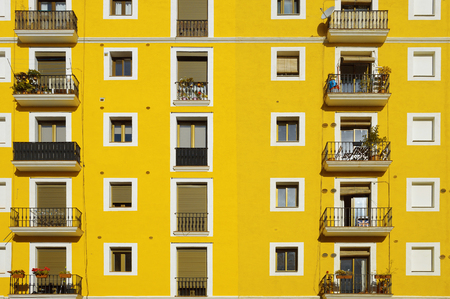 aligned: Yellow facade. Some aligned apartment windows making rows. Sunny day.