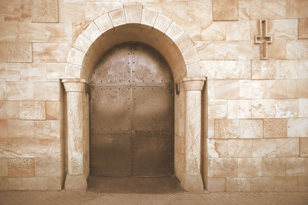 Romanesque chapel entrance with a cross. Arc architecture. Empty copy space for Publisher's text.