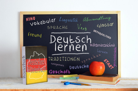 Blackboard in a German classroom with the message LEARN GERMAN and some text