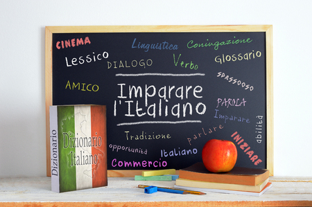 Blackboard in an Italian language classroom with the message LEARN ITALIAN (Imparare l' Italiano) and some other linguistic words. Foto de archivo