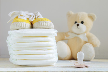 personal hygiene: Some nappies on a white wooden table. Sneakers, a pacifier and a teddy bear. Empty copy space for editors text.