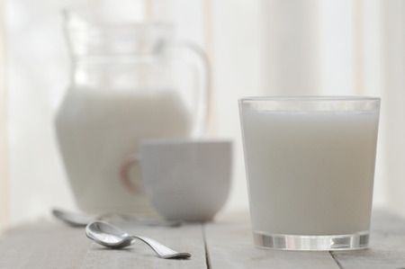 editors: A glass of milk next to a jar and a cup. Empty copy space for Editors text. Stock Photo
