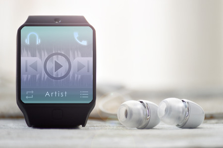 Headphones connected to a smart watch running a music player application. Empty copy space for Editors text. Stock Photo