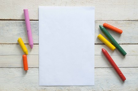 editors: Paper and some crayons on a wooden table in a classroom. Empty copy space for Editors text.