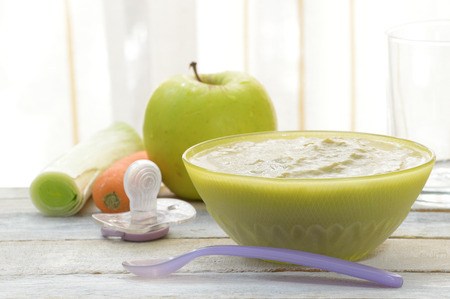 freshly prepared: Freshly prepared baby food served on a bowl on a white wooden table. Empty copy space for Editors text. Stock Photo