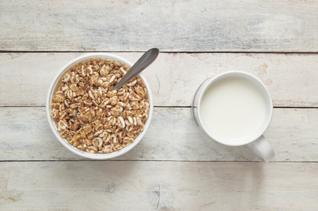 editors: Spoon some cereals from serving bowl at breakfast next to some milk. Empty copy space for Editors text.