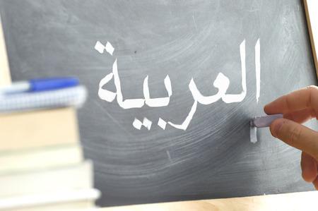 Escritura de la mano en una pizarra en una clase de árabe. Algunos libros y material escolar.