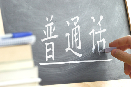 Hand writing on a blackboard in a Chinese class. Some books and school materials. Mandarin language.