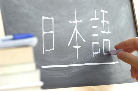 """Hand schrijven van het woord een aantal """"Japans"""" kana syllabary in op een schoolbord in een Japanse klasse. Sommige boeken en schoolmateriaal. Stockfoto"""