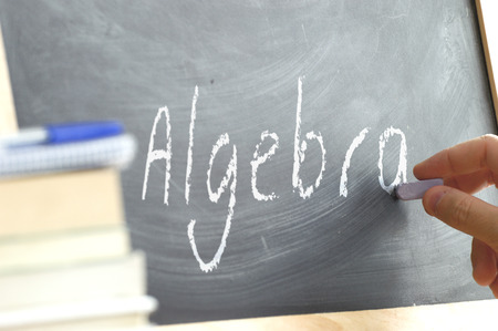 person writing: A person writing in a blackboard During Algebra class in a school. Next, some books.