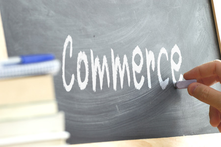 person writing: A person writing a blackboard in class During Commerce in a school. Next, some books. Stock Photo