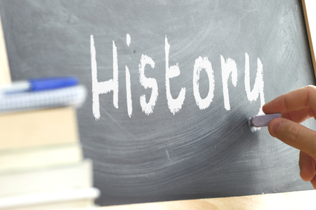 person writing: A person writing a blackboard in History During class in a school. Next, some books.