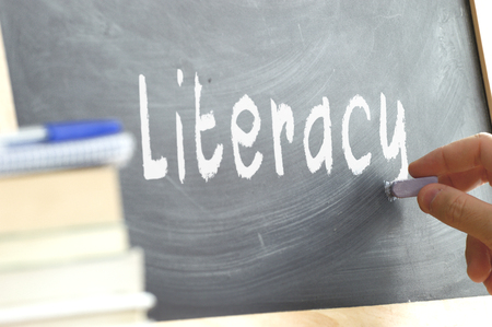 person writing: A person writing in a blackboard in a class Literacy During school. Next, some books. Stock Photo