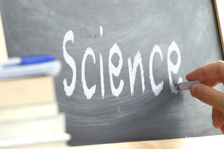 person writing: A person writing in Science During a blackboard in a school class. Next, some books. Stock Photo