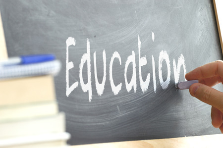 person writing: A person writing the word Education on a blackboard. Some school materials and copy space. Stock Photo