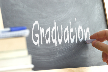 person writing: A person writing the word Graduation on a blackboard. Some school materials and copy space. Stock Photo