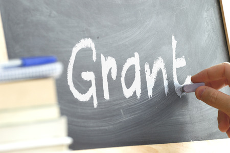 person writing: A person writing the word Grant on a blackboard. Some school materials and copy space Stock Photo