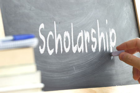person writing: A person writing the word Scholarship on a blackboard. Some school materials and copy space.