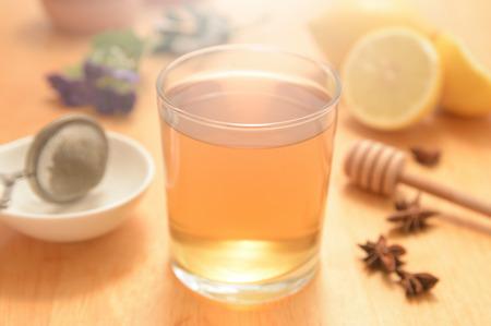 herbolaria: Un vaso de manzanilla con algunos miel y semillas de anís natural en una mesa de madera de una cocina rústica. Algunos cítricos y remedios herbolarios. Foto de archivo