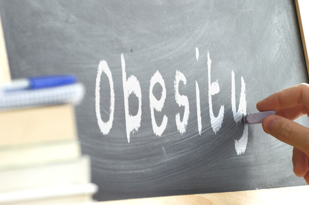 childhood obesity: The word Obesity hand written on a blackboard. Children nutrition concept at school.
