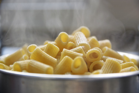 glycemic: Some steaming boiled pasta in a saucepan. Empty copy space for Editors text. Stock Photo