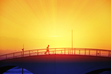 Running Man crossing a bridge next to the beack at sunset. Empty copy space for Editors text.
