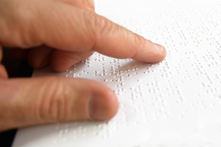 Hand of a blind person reading Braille text some touching the relief. Empty copy space for Editors content.