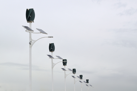 Wind turbines and Solar panels power in a power generation plant. Cloudy sky and empty copy space for Editor's content.