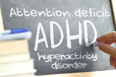 Hand schrijven op een schoolbord in een klas met het woord geschreven op ADHD. Sommige boeken en schoolmaterialen. Let op Deficit Hyperactivity Disorder-concept.