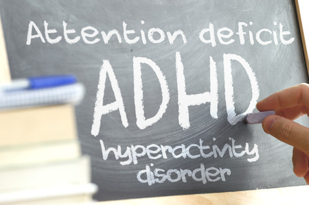 Hand writing on a blackboard in a class With the word written on ADHD. Some books and school materials.Attention Deficit Hyperactivity Disorder concept.