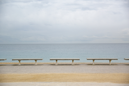 Row of benches next to the sea. Cloudy blue sky. Empty copy space for Editor's text.