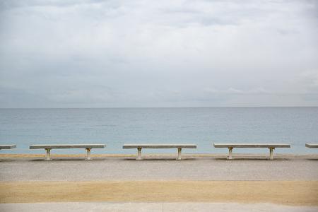 Rij van bankjes naast de zee. Bewolkt blauwe lucht. Leeg kopie ruimte voor de tekst van de redacteur.