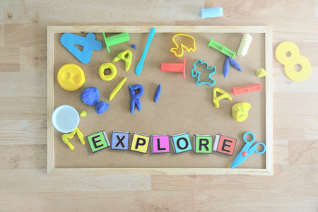 Some colored cube letters on a blackboard in a classroom forming the word EXPLORE. Children education concept.