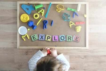 Kind liggend op de vloer spelen met enkele letters samenstellen van het woord kubus EXPLORE. Onderwijs concept. Stockfoto