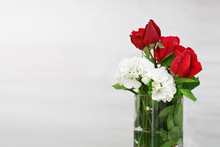 Kristal glazen pot met wat water en rode rozen en witte bloemen. Lege kopie ruimte voor tekst van de redactie.