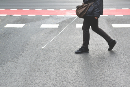 Blind person walking with a stick crossing a pedestrian walkway. Empty copy space for Publisher's text. Foto de archivo