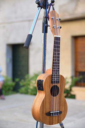 Houten muzikale snaarinstrument ukulele op een tribune voor een concertstraat.