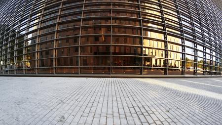 Stedelijke achtergrond. Stoep en gouden glazen gevel met enkele reflecties. Lege sopy-ruimte voor tekst van de redacteur. Stockfoto
