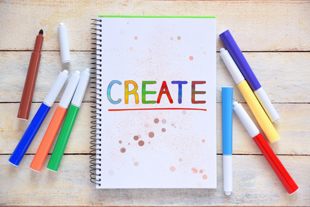 Some markers on a white wooden desktop and a notebook with the word CREATE colorful hand written on it. Empty copy space for Publisher's text.