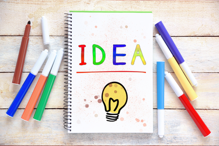 Some markers on a white wooden desktop and a notebook with the word IDEA colorful hand written on it. Empty copy space for Publisher's text. Banque d'images