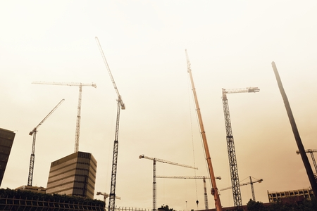 Some tower cranes in the city against the sky. Empty copy space for Publisher's text.